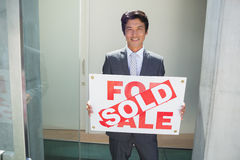 Confident estate agent standing at front door showing sold sign Stock Photo