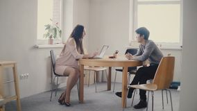 Confident European female lawyer talking to young Japanese man by the table. Multiethnic discussion in modern office 4K.