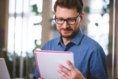Confident executive reading documents at creative office Stock Images