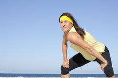 Confident exercising mature woman ocean  Royalty Free Stock Photo