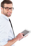 Confident and experienced businessman. Cheerful young man in formalwear working on digital tablet and looking over shoulder while standing isolated on white royalty free stock photo