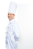 Confident and experienced chef. Confident mature chef in white uniform leaning at the copy space and smiling while standing against white background stock images
