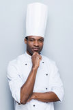 Confident and experienced chef. Confident young African chef in white uniform holding hand on chin and looking at camera while standing against grey background royalty free stock photo