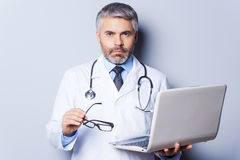 Confident and experienced doctor. Confident mature doctor working holding laptop and looking at camera while standing against grey background stock images