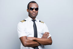 Confident and experienced pilot. Confident African pilot in uniform keeping arms crossed while standing against grey background royalty free stock photos