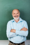 Confident expert teacher looking at camera. Vertical portrait of Confident expert teacher looking at camera while sitting with arms folded with a blank Royalty Free Stock Photo