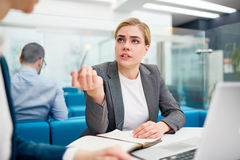 Confident explanation. Businesswoman consulting her colleague at meeting stock image