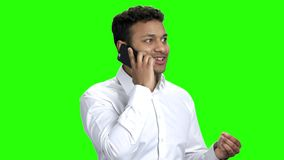 Confident expressive businessman talking on cell phone. Indian businessman celebrating success while talking on phone. Green screen background stock video footage