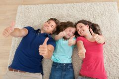 Confident family gesturing thumbs up at home Stock Images