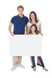 Confident family holding blank billboard Stock Image