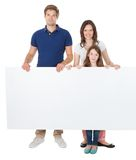 Confident family holding blank billboard. Portrait of confident family holding blank billboard over white background Stock Images