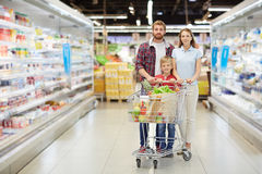 Confident family with shopping cart royalty free stock photography