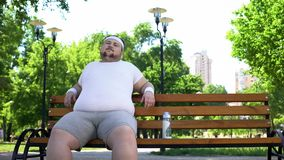 Confident fat man sitting in park, feels happy, contented with life, self-love. Stock photo royalty free stock photo