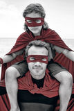 Confident father in superhero costume carrying son on shoulder Stock Images