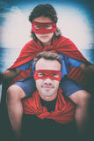 Confident father in superhero costume carrying son on shoulder Royalty Free Stock Image