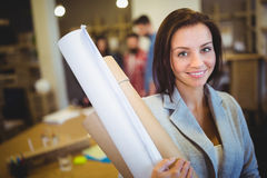 Confident female architect with blueprints in office Stock Photos