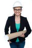 Confident female architect carrying blueprints Stock Images