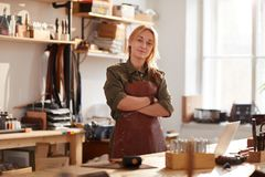 Confident Female Artisan. Warm toned portrait of confident female artisan standing with arms crossed while posing in workshop stock image