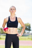 Confident female athlete holding a shot put ball Stock Photos