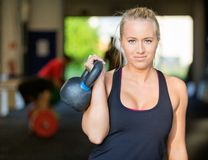 Confident Female Athlete Lifting Kettlebell. Portrait of confident female athlete lifting kettlebell at gym Royalty Free Stock Photography