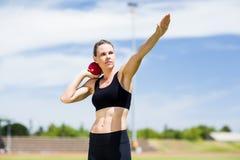 Confident female athlete preparing to throw shot put ball. In stadium Royalty Free Stock Photos