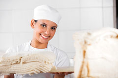 Confident Female Baker With Bread Slices Stock Photography