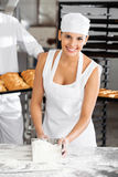 Confident Female Baker Holding Flour Scoop At Royalty Free Stock Image