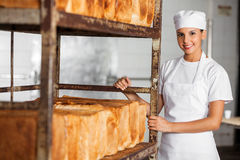 Confident Female Baker Standing By Bread Rack Stock Images