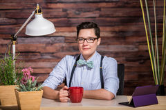 Confident Female in Bowtie with Mug Stock Image
