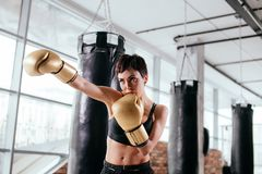 Confident female boxer is preparing for boxing match. Being fond of boxing. art of self-defense Stock Photos