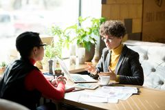 Confident female business analyst sharing report results with co. Serious confident female business analyst with curly hair wearing stylish jacket sitting at stock photography