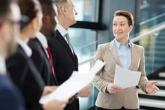 Explaining report points. Confident female business leader with papers making report about the latest upgrades of financial rates for her business team at royalty free stock photo
