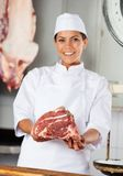 Confident Female Butcher Holding Red Meat Royalty Free Stock Photos