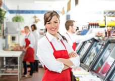 Confident Female Butcher Standing Arms Crossed. Portrait of confident female butcher standing arms crossed with colleagues in background Stock Photos