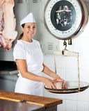 Confident Female Butcher Weighing Meat On Scale Stock Photos