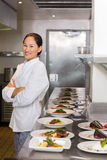 Confident female chef besides cooked food in row at kitchen. Portrait of a confident female chef standing besides cooked food in row at the kitchen stock images