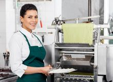 Confident Female Chef Holding Ravioli Pasta Tray Royalty Free Stock Photography