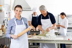 Confident Female Chef Holding Rolling Pin While Royalty Free Stock Photos