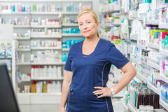 Confident Female Chemist With Hand On Hip. Portrait of confident female chemist with hand on hip standing in pharmacy Royalty Free Stock Photos