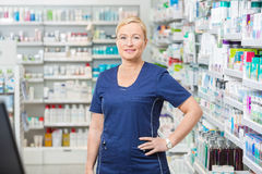 Confident Female Chemist With Hand On Hip. Portrait of confident female chemist with hand on hip standing in pharmacy Royalty Free Stock Images
