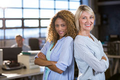 Confident female colleagues standing back to back. Portrait of confident female colleagues standing back to back in creative office Royalty Free Stock Photo