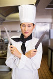 Confident female cook holding knives in kitchen Royalty Free Stock Photo