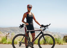 Confident female cyclist standing with her bicycle Royalty Free Stock Photo
