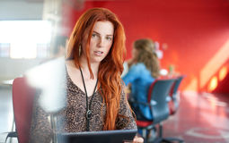Confident female designer working on a digital tablet in red creative office space. Casual portrait of a redhead business women using technology in a bright and stock photo