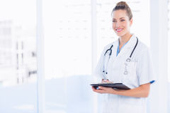 Confident female doctor with clipboard in hospital Stock Photography