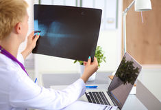 Confident female doctor examining accurately a rib. Cage x-ray royalty free stock photography