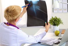 Confident female doctor examining accurately a rib. Cage x-ray stock photography