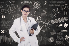 Confident female doctor hold e-tablet on written blackboard Stock Photos