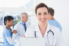 Confident female doctor holding clipboard Stock Photography