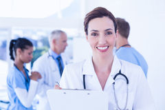 Confident female doctor holding clipboard Stock Photo